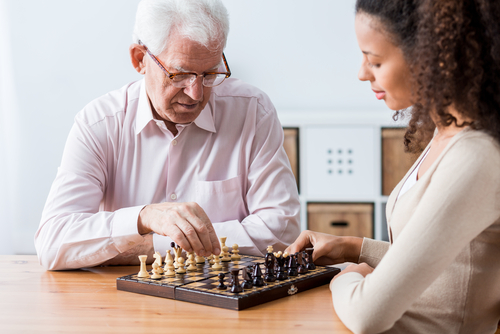 young woman playing chess with elderly man