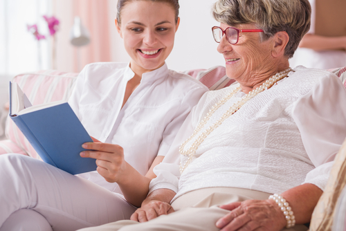 younger woman reading to elderly woman