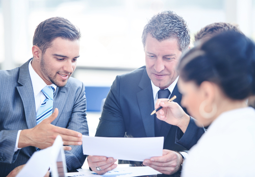 manager and employees reviewing paperwork