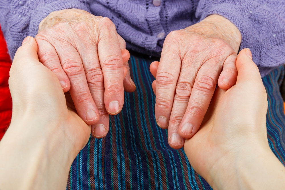 younger person holding the hands of an older person