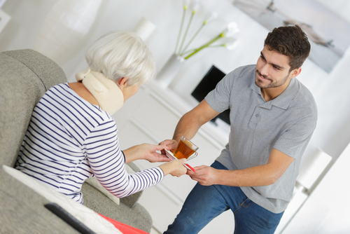 younger man serving tea to older woman